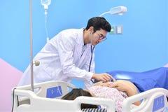 Asiatischer Doktor, der schwangere Frau mit Stethoskop überprüft Lizenzfreie Stockfotografie