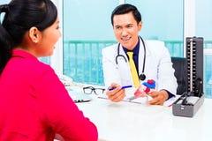 Asiatischer Doktor mit Patienten in der medizinischen Chirurgie Lizenzfreie Stockbilder