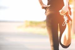 Asiatischer Eignungsfrauenläufer, der Beine vor Lauftraining im Freien im Park ausdehnt stockbilder