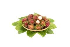 Asiatischer Frucht Rambutan auf Blättern und auf weißem Hintergrund Stockfotos