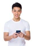 Asiatischer Gebrauch des jungen Mannes des Mobiltelefons Stockfotografie