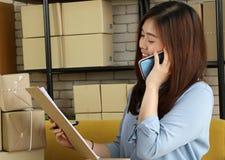 Asiatischer Geschäftsfrau-Gebrauch Smartphoneanruf zum Kunden für Auftragsprodukt mit glücklichem Gesicht schreiben stockfotografie