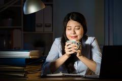 Asiatischer Geschäftsfrau-Getränkkaffee, der über die Zeit hinaus Spät- bearbeitet Lizenzfreie Stockfotos