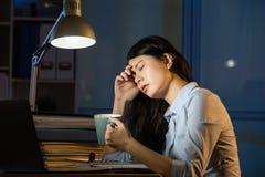 Asiatischer Geschäftsfrau-Getränkkaffee, der La über die Zeit hinaus bearbeitend erneuert Stockfotografie