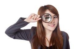 Asiatischer Geschäftsfraublick durch Lupe und Lächeln Lizenzfreies Stockbild