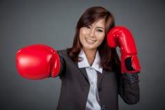 Asiatischer Geschäftsfraudurchschlag mit Boxhandschuhfokus auf dem Handschuh Lizenzfreies Stockfoto