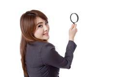 Asiatischer Geschäftsfraugebrauchs-Lupenblick zurück zu Kamera Stockbilder