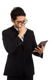 Asiatischer Geschäftsmann denken mit Tablet-PC Lizenzfreie Stockfotografie