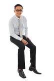 Asiatischer Geschäftsmann, der auf einem transparenten Block sitzt Stockbild