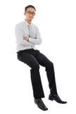 Asiatischer Geschäftsmann, der auf einem transparenten Block sitzt Lizenzfreie Stockbilder