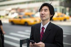 Asiatischer Geschäftsmann, der auf Mobiltelefon simst Lizenzfreie Stockbilder