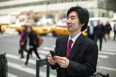 Asiatischer Geschäftsmann, der auf Mobiltelefon simst Lizenzfreie Stockfotografie