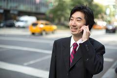Asiatischer Geschäftsmann, der auf Mobiltelefon spricht Stockfotografie