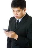 Asiatischer Geschäftsmann, der das Mobile lokalisiert betrachtet Lizenzfreie Stockbilder