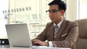 Asiatischer Geschäftsmann, der den Verkaufszahlen auf dem Computer intensiv betrachtet lizenzfreie stockfotografie
