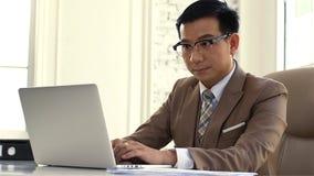 Asiatischer Geschäftsmann, der den Verkaufszahlen auf dem Computer intensiv betrachtet lizenzfreies stockfoto