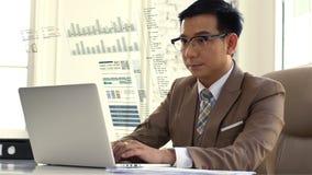 Asiatischer Geschäftsmann, der den Verkaufszahlen auf dem Computer intensiv betrachtet stockbilder