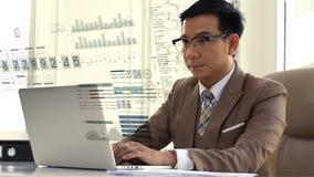 Asiatischer Geschäftsmann, der den Verkaufszahlen auf dem Computer intensiv betrachtet lizenzfreie stockbilder
