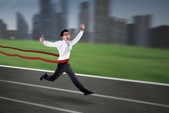 Asiatischer Geschäftsmann, der die Ziellinie kreuzt Stockfoto