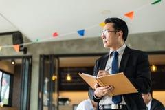 Asiatischer Geschäftsmann, der ein Buch und einen Stift steht und hält, um einen Unternehmensplan zu schreiben lizenzfreies stockbild