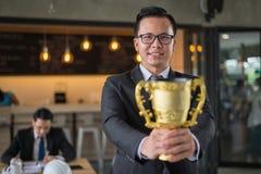 Asiatischer Geschäftsmann, der eine goldene Trophäenschale zu nettem und gefeiert seinem erfolgreich in der Karriere und im Auftr lizenzfreie stockfotos