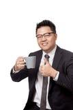 Asiatischer Geschäftsmann, der einen Becher Kaffee und Daumen hochhält Lizenzfreies Stockbild