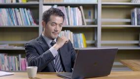 Asiatischer Geschäftsmann, der im Büro arbeitet stock footage