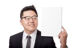 Asiatischer Geschäftsmann, der leeres Zeichen auf seiner Schulter betrachtet Stockfotografie