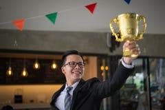 Asiatischer Geschäftsmann, der oben Hand anhebt und eine goldene Trophäenschale zu nettem und gefeiert seinem erfolgreich in der  stockfotos