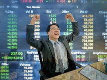 Asiatischer Geschäftsmann, der sehr glückliches weil seine Börse g sitzt lizenzfreie stockbilder