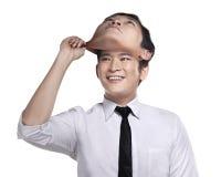 Asiatischer Geschäftsmann entfernen seine andere Gesichtsmaske Lizenzfreie Stockfotografie