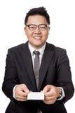 Asiatischer Geschäftsmann geben einer weißen Karte mit beiden Hand Stockbild