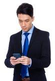 Asiatischer Geschäftsmann gelesen auf Mobiltelefon lizenzfreie stockbilder