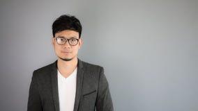 Asiatischer Geschäftsmann im schwarzen Anzug mit grauem Hintergrund lizenzfreie stockbilder