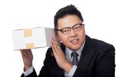 Asiatischer Geschäftsmann ist neugierig, was innerhalb eines Kastens und eines Lächelns Stockfoto