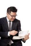 Asiatischer Geschäftsmann las ein Buch mit Lupe Stockfotos