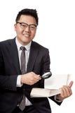 Asiatischer Geschäftsmann mit Buch und Lupe Lizenzfreies Stockbild