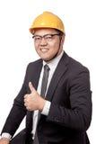 Asiatischer Geschäftsmann mit dem gelben Hardhatdaumen hoch und Lächeln Lizenzfreies Stockbild
