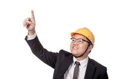 Asiatischer Geschäftsmann mit dem gelben Hardhatpunkt hoch und Lächeln Lizenzfreie Stockfotos
