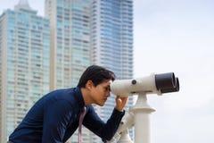 Asiatischer Geschäftsmann mit den Ferngläsern, die Stadt betrachten Stockbilder