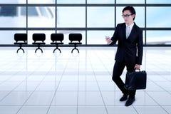 Asiatischer Geschäftsmann mit Smartphone im Flughafen stockfotografie
