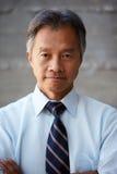 Asiatischer Geschäftsmann Standing Against Wall im modernen Büro Lizenzfreies Stockfoto