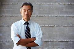 Asiatischer Geschäftsmann Standing Against Wall im modernen Büro Stockbilder