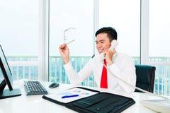 Asiatischer Geschäftsmann am Telefon, das im Büro arbeitet Stockfotos