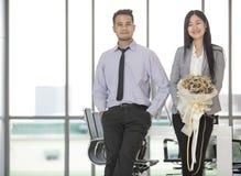 Asiatischer Geschäftsmann und Geschäftsfrau flirtet im modernen Büro stockbild
