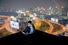 Asiatischer Geschäftsmann unter Verwendung des Telefons und des Laptops mit Stadthintergrund, Stockfotografie