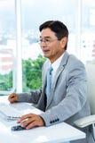 Asiatischer Geschäftsmann unter Verwendung seines Computers Stockbild