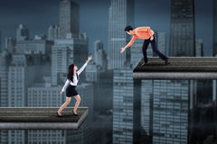 Asiatischer Geschäftsmann, welche einer Geschäftsfrau hilft Stockbilder