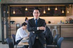 Asiatischer Geschäftsmannabnutzungsschwarzanzug, der zur Kamera Kaffeestube, erfolgreiches Konzept des Geschäfts steht und betrac stockfotografie
