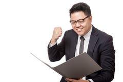Asiatischer Geschäftsmannblick auf einen Ordner glücklich mit Erfolg Stockbilder